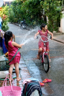 The girl on the bike couldn't get enough of being hosed off her friend.